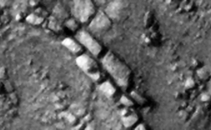 Two rows of rectangular megalithic blocks, smaller features or knobs can be seen on two of the blocks
