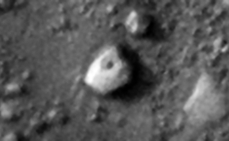 Strange multi-sided megalithic block or perhaps craft, note the dark spot in the center of the hexagon shaped top