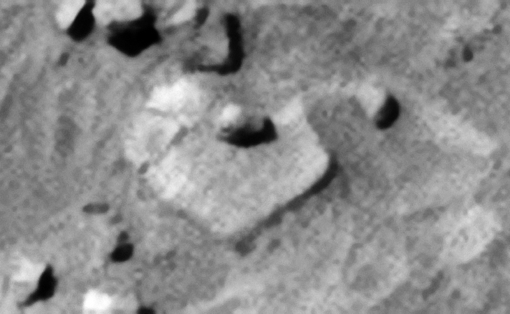 Another strange feature or knob with small dome-shaped part in the center on top of a large, hexagonal-shaped slab with rounded corner