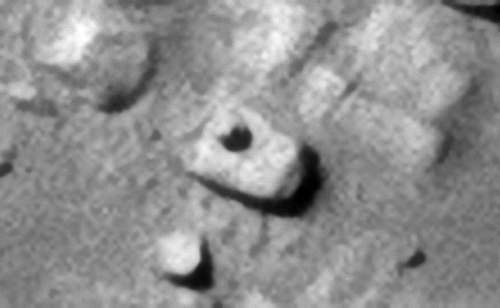 Another small dome-shaped feature with smaller circular part on top of the feature located on the surface of a rectangular block