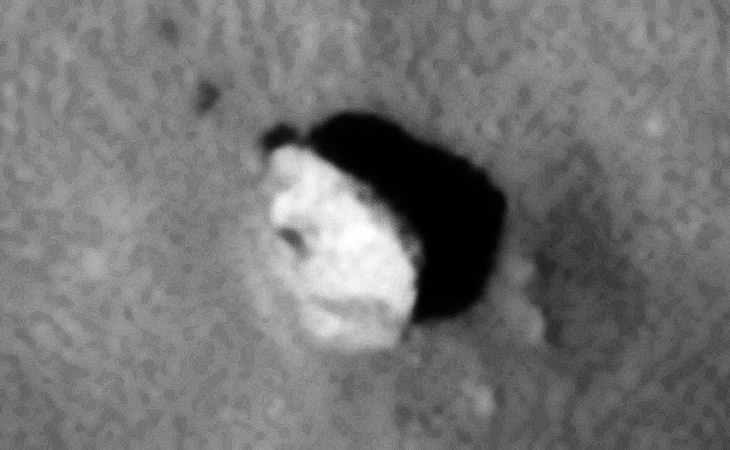 Partially buried, disc-like object with a small dark dome on the side