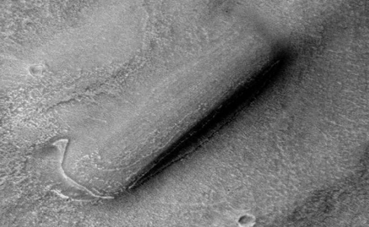 The '2001: A Space Odyssey Monolith' lying on the Martian surface covered in sand and dust
