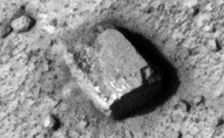 Rectangular megalith with flat straight sides 10 metres by 8 metres, a small square has been cut into the bottom right corner
