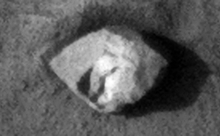 Rectangular megalith with two flat straight sides 18 metres by 12 metres, a hole seems to be cut into one corner, the right part seems to be covered in a white, reflective material
