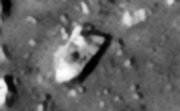 More metallic-type wreckage and parts of a destroyed machine? Some of the edges are straight, well defined, with multiple right-angles and there seems to be a small dome-like feature and other pipe-like features on the top